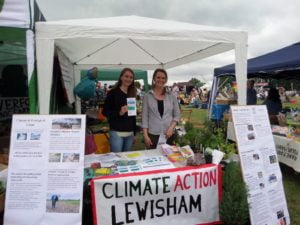 Two members behind table with Climate Action Lewisham bannerat festival stall
